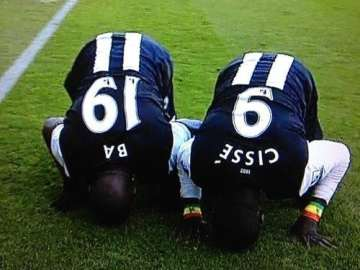 Demba Ba and Papiss Cisse prostrate themselves.